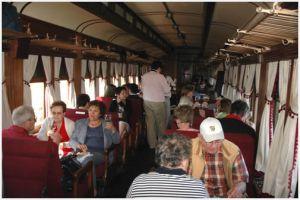 Sus vagones han sido reacondicionados preservando los detalles originales y apreciamos el cálido interior de madera, con asientos dobles de pana roja, tulipas, ventanillas y portaequipaje haciendo juego.